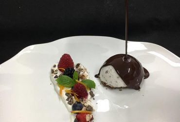 Semifreddo al torroncino (nougat parfait) served with warm chocolate sauce (70%) and spiced nougat chips
