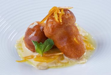 Baba mignon soaked in rum with candid orange peel, almonds and Grand Marnier sauce